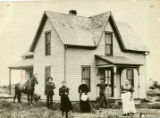 Early photograph of J. W. Browning family outside of their two-story wooden farm house, built in...